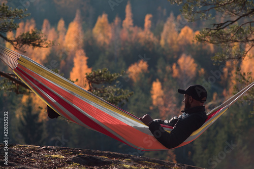 Fotografie, Obraz  A man sits in a hammock and admires the autumn forest