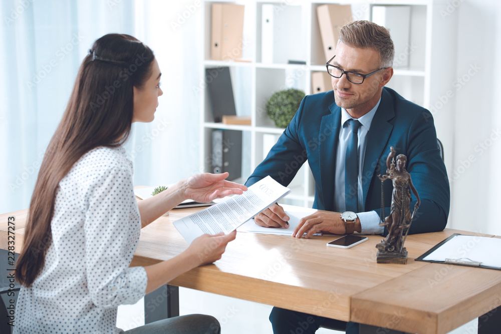 Fototapeta lawyer and client looking at each other while discussing papers in office