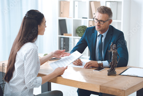 Photographie lawyer and client looking at each other while discussing papers in office