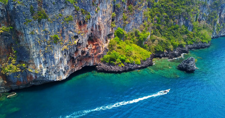 Single Boat Moving Past Steep Island Cliffs and Coral Reef in Phi Phi Don, Thailand - Aerial Overhead View