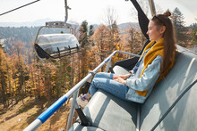 Young Woman Sits In Cable Car Elevator And Smiles While Looks At Autumn Landscape