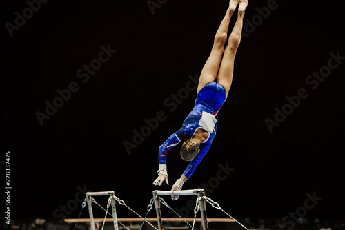 uneven bars performing female gymnast at artistic gymnastics