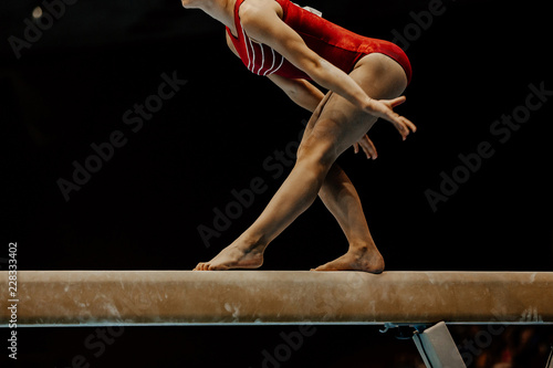 exercise balance beam female gymnast on black background