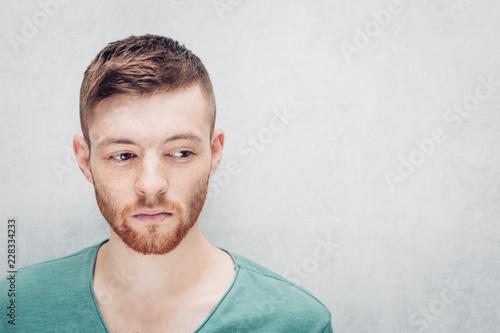 Sad young man on a gray background. Closeup portrait.