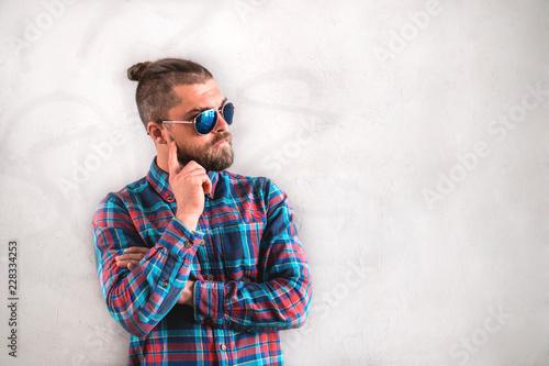 Valokuva  Handsome stylish man is standing near wall.