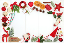 Christmas Background Border Composition With Traditional Symbols Of Bauble Tree Decorations, Candy Canes, Mince Pies, Fruit, Spices, Winter Flora, Ribbon And Gift Tag On Rustic White Wood. Top View.