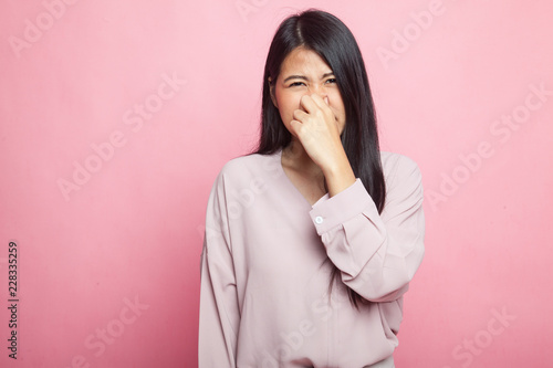 Fotografie, Tablou  Young Asian woman  holding her nose because of a bad smell.