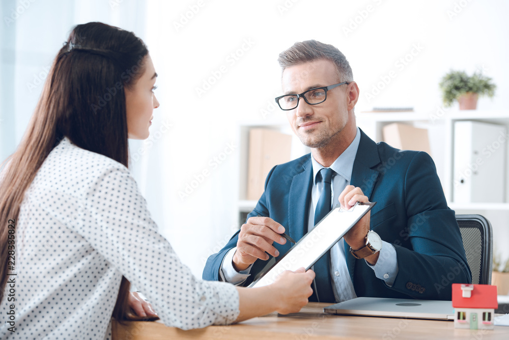 Fototapety, obrazy: insurance agent pointing at clipboard in clients hand at tabletop in office, house insurance concept