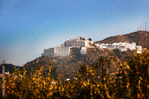 The mountainside village of Mojacar Pueblo taken from the countryside below it with palms and yellow flowers. This is a popular holiday destination.