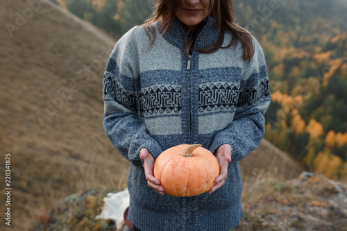Photo  Portrait of young beautiful girl in warm sweater with pumpkin on background of a