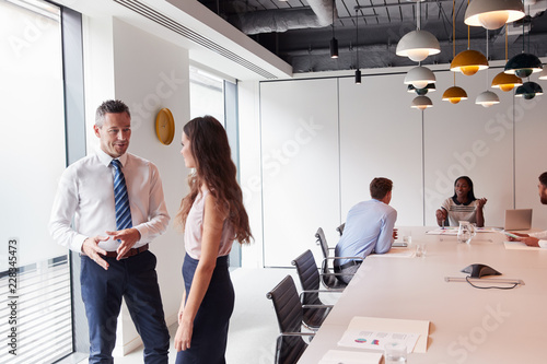 Amazing Businessman And Businesswoman Standing In Modern Boardroom Beutiful Home Inspiration Ommitmahrainfo