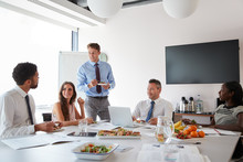Businessmen And Businesswomen Meeting In Modern Boardroom Over Working Lunch