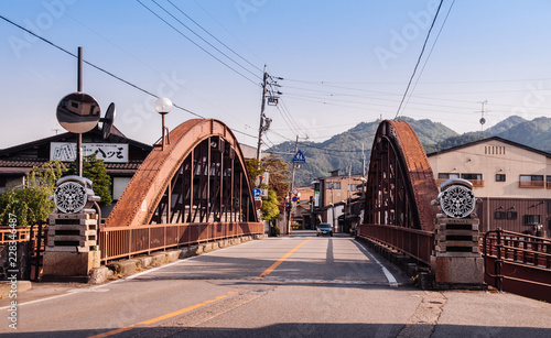Foto  Old houses and historic iron truss bridge over river and mountain view of Hida Furukawa old town, Gifu