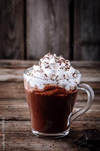 Hot chocolate drink with whipped cream in a glass on a wooden background
