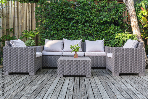 Poster Jardin Large terrace patio with rattan garden furniture in the garden on wooden floor.