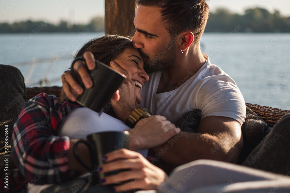 Fototapety, obrazy: Boyfriend kissing his smiling girlfriend in forehead by the river