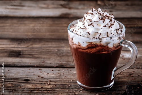 Foto op Plexiglas Chocolade Hot chocolate drink with whipped cream in a glass on a wooden background