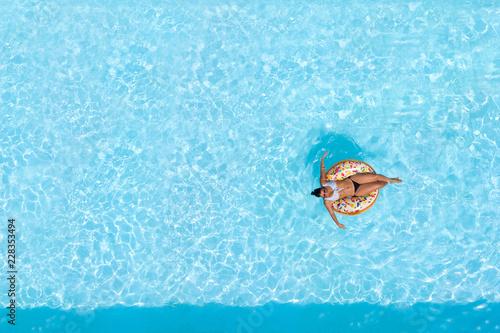 Woman on a donut buoy in a blue water swimming pool aerial view from above Canvas Print