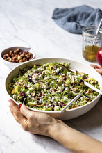 Woman's Hand Holding Brussels Sprouts Salad In Bowl