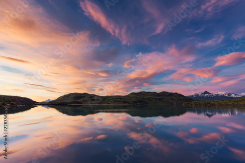 Clouds reflecting off of water during sunset with mountains in the background
