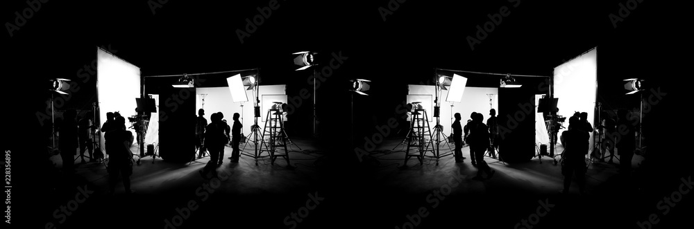 Fototapeta Silhouette images of video production behind the scenes or b-roll or making of TV commercial movie that film crew team lightman and cameraman working together with director in big studio