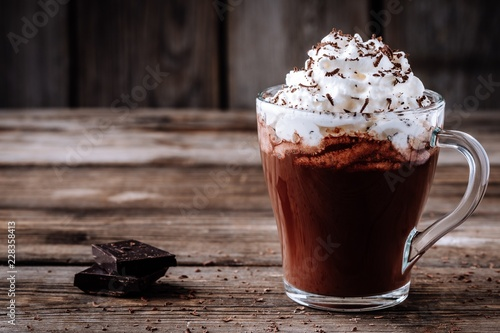Fond de hotte en verre imprimé Chocolat Hot chocolate drink with whipped cream in a glass on a wooden background