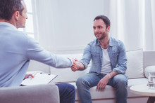 Gratitude. Pleased Positive Bearded Man Shaking Hands With Professional Psychiatrist While Being Extremely Thankful To Him For A High Quality Assistance
