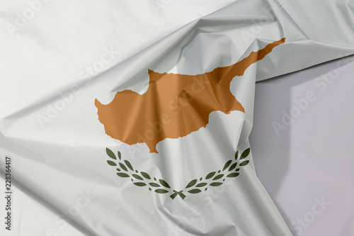 Cyprus fabric flag crepe and crease with white space, an outline of the country of Cyprus above twin olive branches.