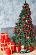 Christmas background with Christmas fir tree, red gift boxes decorated with golden ribbon and child toys on floor, copy space. Winter holidays concept
