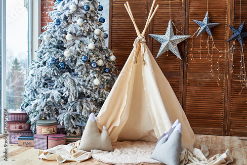 Fotografía Christmas tree with gifts and wigwam near window in child room, copy space