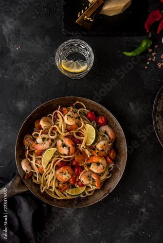 Fototapeta Makaron z krewetkami, pomidorkami koktajlowymi, papryczką chili i natką pietruszki. Podany na patelni. Ciemne tło. widok z góry. obraz