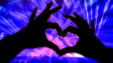 Silhouette hands in heart shape during a concert - 228384057