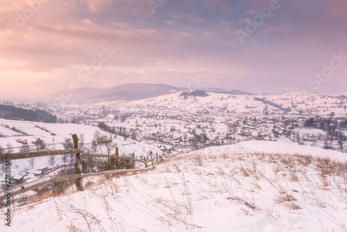 Deurstickers Lichtroze Beautiful winter landscape in soft sunset light, alpine valley surrounded by wooded mountains, Carpathians