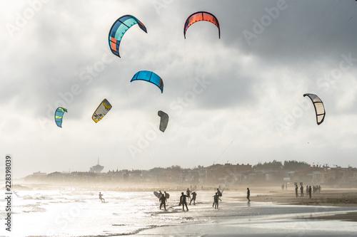 un groupe de kitesurf en bord de plage avec un ciel d'automne
