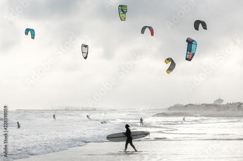 un surfer passe devant des kitesurf sous un ciel nuageux