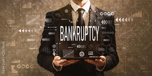 Bankruptcy with businessman holding a tablet computer on a dark vintage backgrou Wallpaper Mural