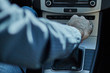 Closeup of a man in a car changing gear with his hand.