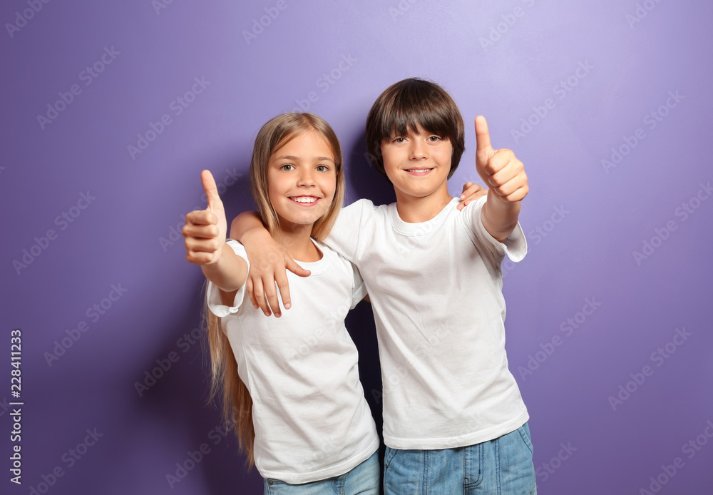 Fototapeta Hugging boy and girl in t-shirts showing thumb-up on color background
