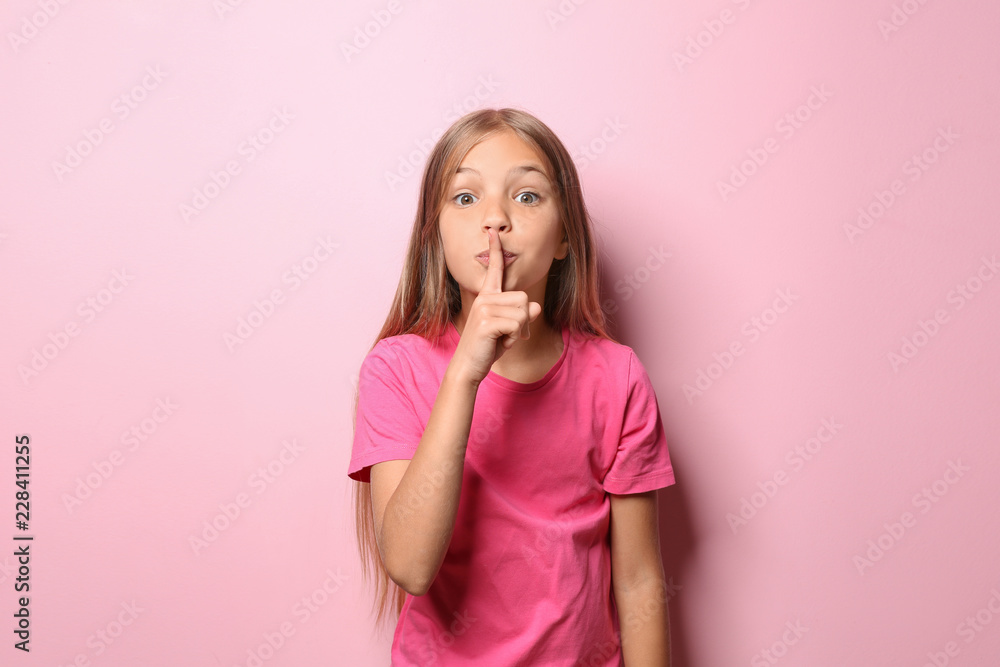 Fototapeta Little girl in t-shirt showing silence gesture on color background