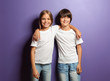 Leinwandbild Motiv Boy and girl in t-shirts hugging each other on color background