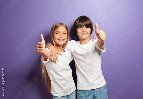 Obraz Hugging boy and girl in t-shirts showing thumb-up on color background - fototapety do salonu