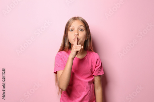 Photo  Little girl in t-shirt showing silence gesture on color background
