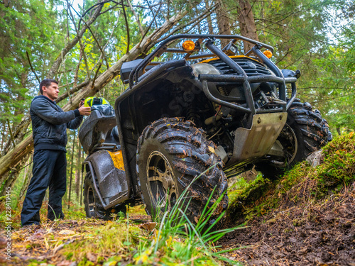 Fototapety, obrazy: A man travels in an all-terrain vehicle. Forest. ATV. Leisure. A man goes on the road on the ATV. The traveler takes off his helmet. Off-road.