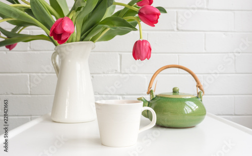 White cup on small table with green teapot and red tulips in jug at rear (selective focus)