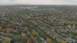 Aerial footage over a sub-division outside a city with large buildings in the distance on a cool autumn evening