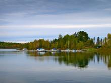 Beautiful Minnesota Lake With Reflection Of Marina And Boats On Cloudy Day
