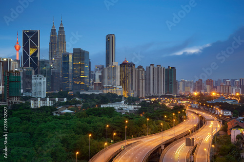 Kuala Lumpur night cityscape skyline with illuminated highway flyover road