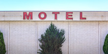 Motel Sign On A White Brick Building With Trees