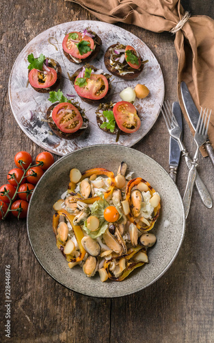Salad with mussels and sweet peppers, canapes with tomatoes. Mediterranean Kitchen