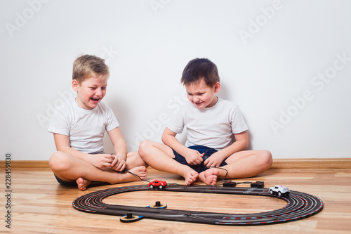 two cheerful boys in white t-shirts start toy cars